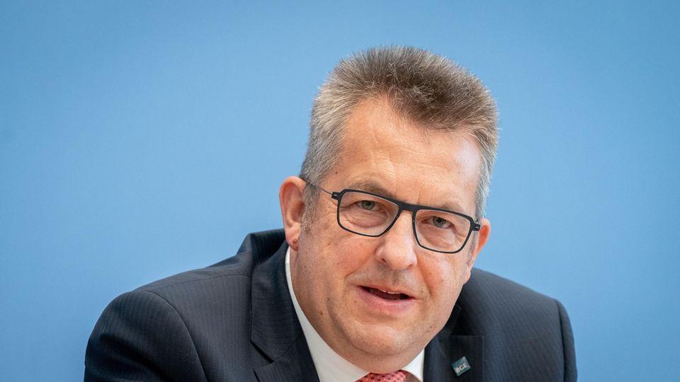 Ein Mann in Anzug und Krawatte sitzt vor einer blauen Wand. Er trägt eine markante schwarze Brille und einen Bürstenschnitt