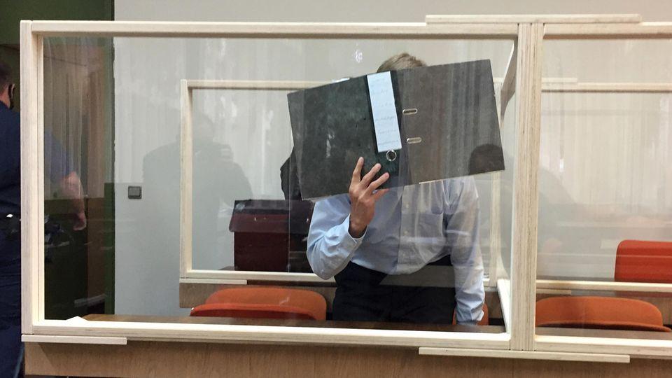 Nachrichten aus Deutschland: Der Angeklagte verdeckt sein Gesicht mit einem Ordner