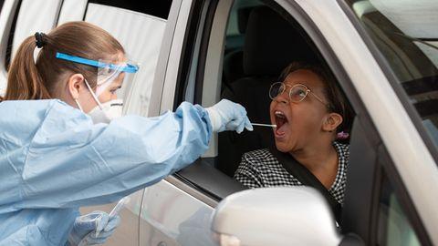 Eine Frau in medizinischer Schutzkleidung steckt einer anderen auf dem Beifahrersitz eines Autos ein Wattestäbchen in den Mund