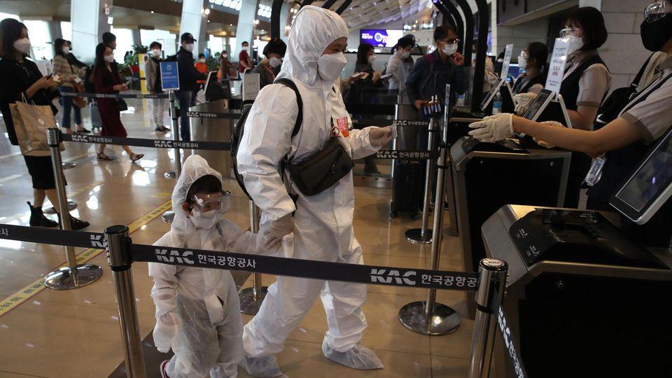 Seoul, Südkorea. Eine Mutter und ihr Kind tragenSchutzanzüge, während sie an Bord eines Fluges steigen. In Südkorea steht am 1. Oktober dasChuseok-Fest an, das Äquivalent zum Erntedankfest. Viele verreisen in dieser Zeit, um ihre Familien zu besuchen. Daher befürchten die südkoreanischen Behörden, dass die Zahl der Corona-Infektionen stark steigen könnte.