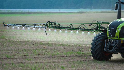 Ein Traktor versprüht eine Flüssigkeit auf einem Feld
