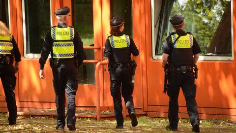 Polizisten gehen auf eine Schule zu