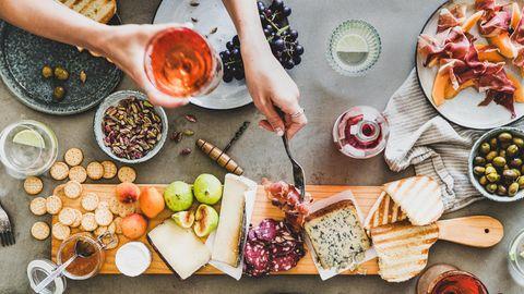 Intervallfasten und Abnehmen: Ein voll gedeckter Tisch mit Käse und Wein