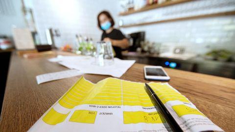 Auf einem Holztisch liegt ein Zettel mit gelben Feldern für Name und Adresse. Dahinter steht unscharf eine Restaurantangestellte