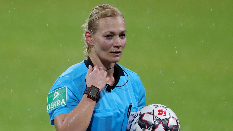 Bibiana Steinhaus steht im hellblauen Schiedsrichter-Trikot im Regen auf dem Rasen und hält einen Ball im linken Arm