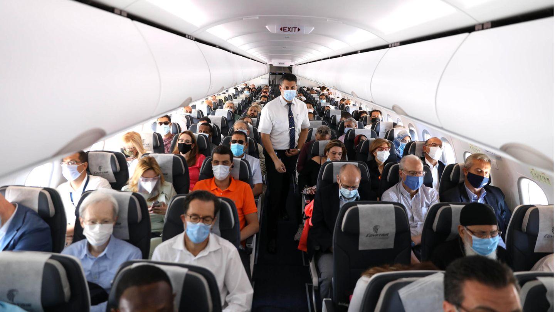 Fliegen in Zeiten von Corona:Passagiere tragen einen Mund-Nasen-Schutz