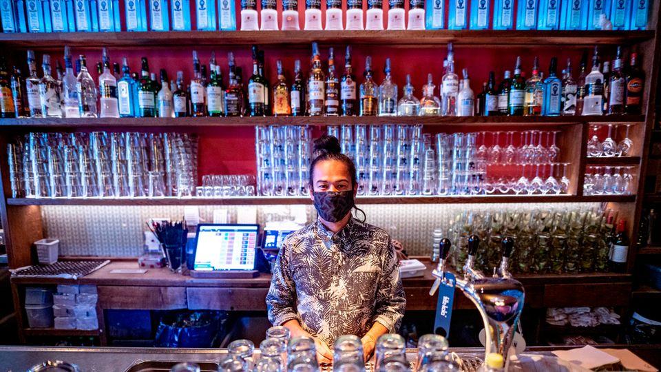 """Tristan Alhambra, Geschäftsleiter der Bar """"Katze"""" im Hamburger Schanzenviertel, steht hinter dem Tresen"""