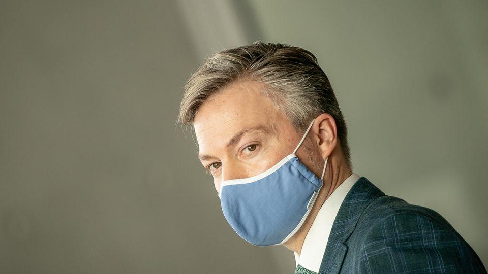 Ein Mann mit grauen Seitenscheitel und hellblauem Mund-Nasen-Schutz trägt einen Anzug