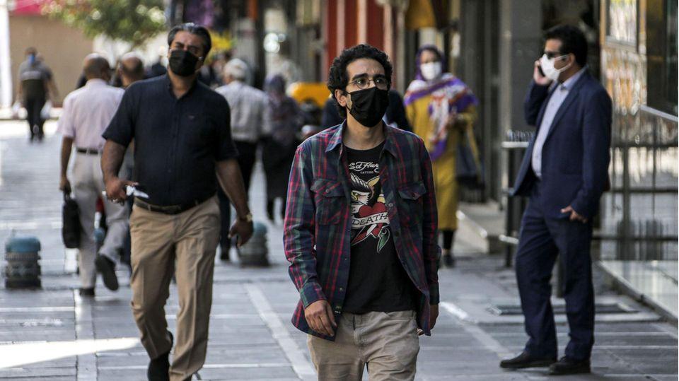 Passanten gehen mit Masken an einer Geschäftsstraße in Irans Hauptstadt Teheran entlang. Das Land ist schwer gebeutelt von der Coronakrise.