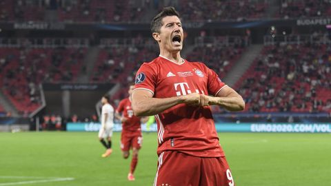 Im roten Bayern-Dress steht Robert Lewandowski auf dem Platz und jubelt mit den Händen vor der Brust