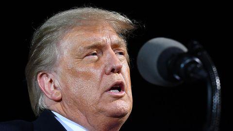 US-Präsident Donald Trump steht hell angeleuchtet in einer Halle und spricht in ein Mikrofon