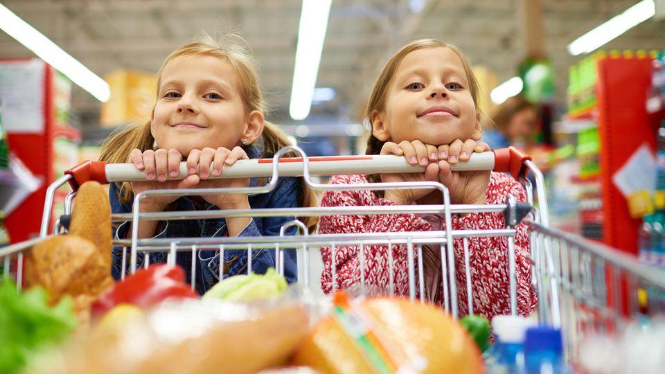 Zwei Mädchen umklammern einen Griff am Einkaufswagen