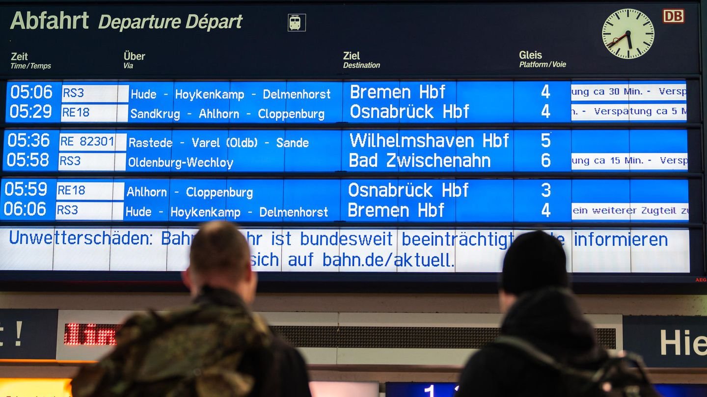 Verspätungen: Reisende stehen am Morgen am Bahnhof und schauen zur Anzeigetafel der Deutschen Bahn:
