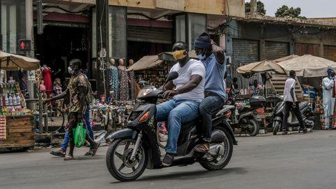 Coronavirus Afrika: Zwei Männer mit Schutzmasken fahren zusammen auf einem Motorroller
