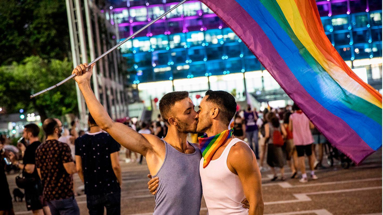 Zwei schwule Männer küssen sich auf der Straße und schwenken eine Regenbogenfahne
