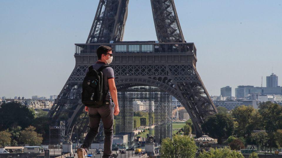 Ein junger Franzose läuft vor dem Pariser Eiffelturm. Er trägt einen Mund-Nasen-Schutz.