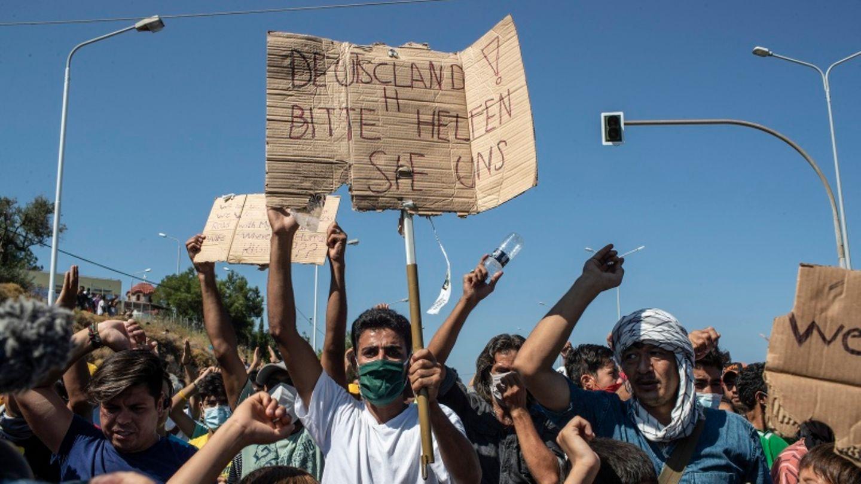 """Griechenland, Lesbos: Flüchtling hält ein Plakat mit der Aufschrift """"Deutschland, bitte helfen Sie uns""""."""