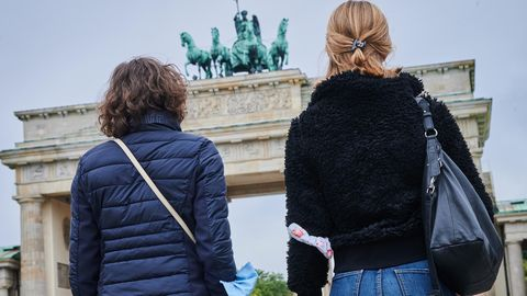 Berlin: Zwei Frauen gehen mit Mund-Nasenschutz am Oberarm vor dem Brandenburger Tor