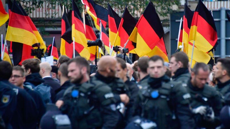 Polizisten bei einer Demonstration; im Hintergrund sind zahlreiche Deutschlandfahnen zu sehen.
