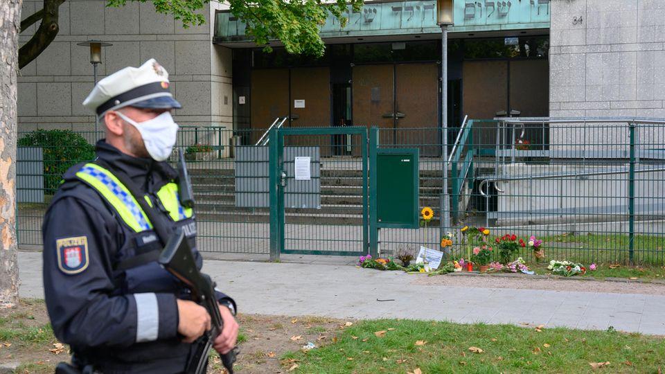 Ein Polizist steht vor der Synagoge in Hamburg, vor der ein jüdischer Student angegriffen wurde. Vor dem Tor liegen Blumen.