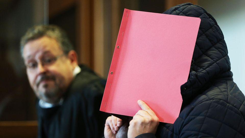 Landgericht Köln: Der Angeklagte verdeckt sein Gesicht mit einem roten Umschlag