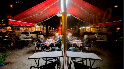 Gäste sitzen am Abend vor einer Kneipe im Berliner Bezirk Wilmersdorf
