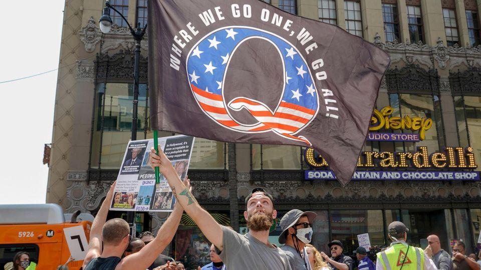 """Ein Demonstrant schwenkt eine Flagge mit einem """"Q"""" in Muster der US-Flagge und dem Spruch """"Where we go one, we go all"""""""