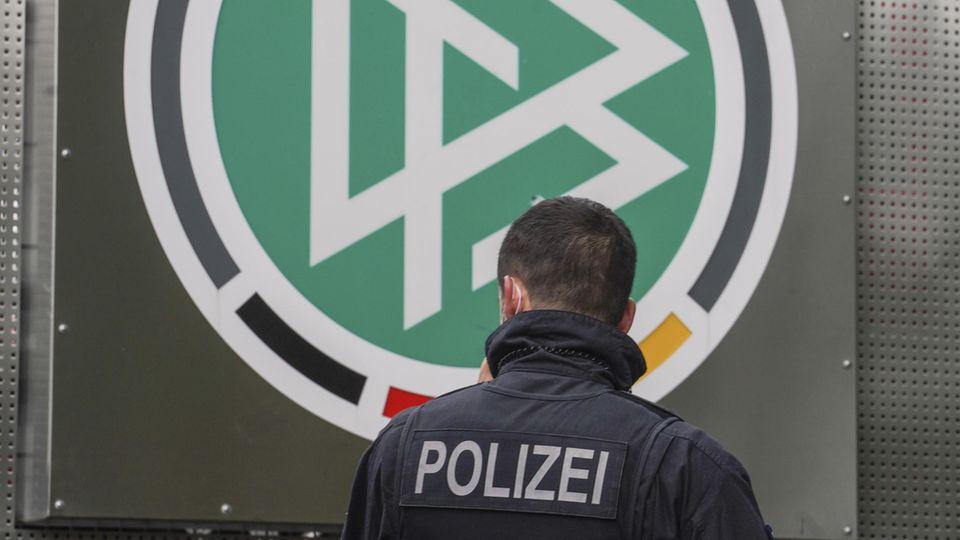 Razzia beim DFB: Ein Polizeibeamter steht am Logo des DFB vor der Zentrale in Frankfurt/Main