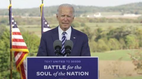 US-Präsidentschaftskandidat steht unter freiem Himmel an einem Rednerpult. Neben ihm US-Flaggen