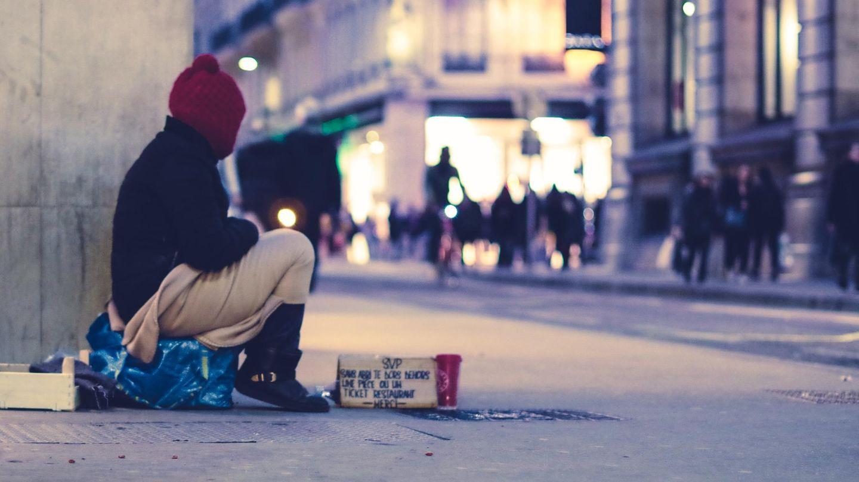 Ein Obdachloser sitzt auf der Straße