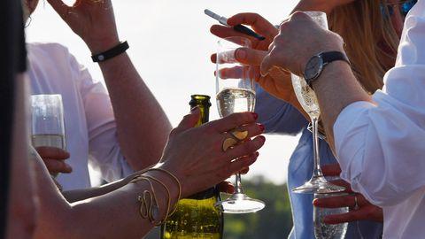 Partygäste halten Gläser mit Prosecco in den Händen.