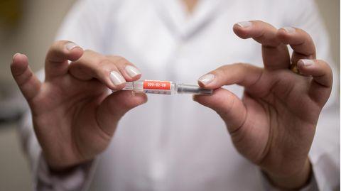 EineMitarbeiterin zeigt den Impfstoff gegen SARS-CoV-2 des chinesischen Pharmakonzerns Sinovac
