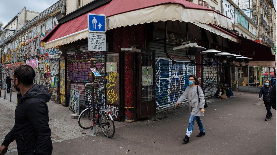 Frankreich, Paris: Passanten mit Mund-Nasen-Bedeckungen gehen an einer geschlossenen Bar vorbei