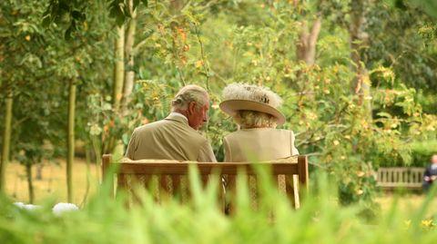 Camilla und Charles auf einer Bank sitzend