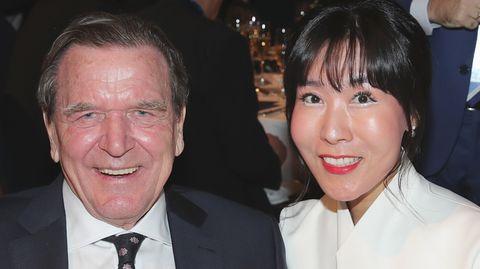 Altkanzler Gerhard Schröder im Anzug und seine Frau Soyeon Kimim weißen Blazer lächeln in die Kamera