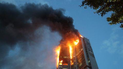 Von unten ist ein Hochhaus zu sehen, dessen oberes Drittel in Flammen steht. Eine schwarze Rauchwolke weht von Gebäude weg