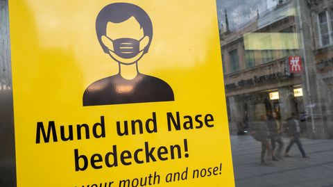 Ein Schild fordert zum Tragen eine Mund-Nasen-Bedeckung auf