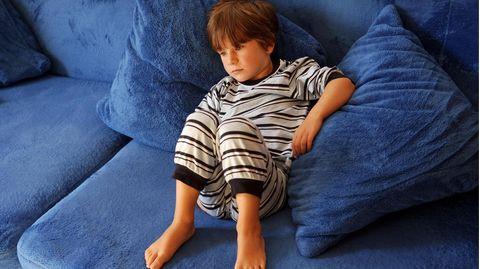 Junge im Schlafanzug liegt auf dem Sofa