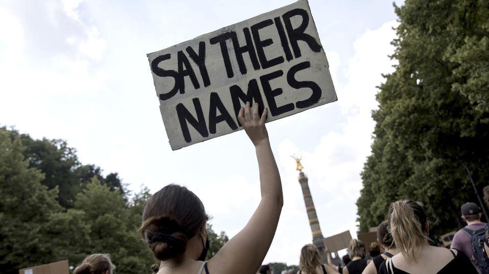 """Anti-Rassismus-Demo in Berlin: Eine Frau hält ein Schild mit der Aufschrift """"Say their names"""" hoch"""