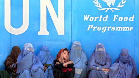 Frauen sitzen vor dem Gebäude des UN-Welternährungsprogramms (WFP) in Kabul und warten auf die Verteilung von Lebensmitteln