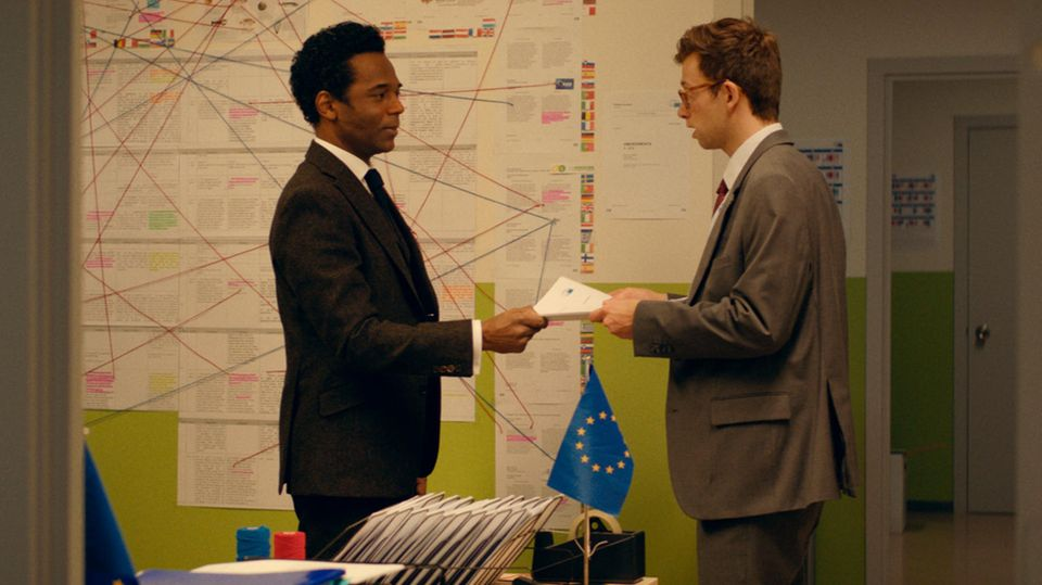 """Szene aus """"Parlament"""": Samy übergibt Eamon einen Stapel Papiere"""