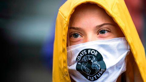 Greta Thunberg steht mit Mund-Nasen-Schutz und gelber Kapuze vor mehreren Mikrofonen
