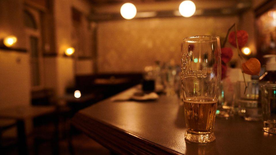 Ein halb geleertes Bier und andere benutzte Gläser stehen kurz nach der Sperrstunde in einer Bar in Neukölln auf dem Tresen.