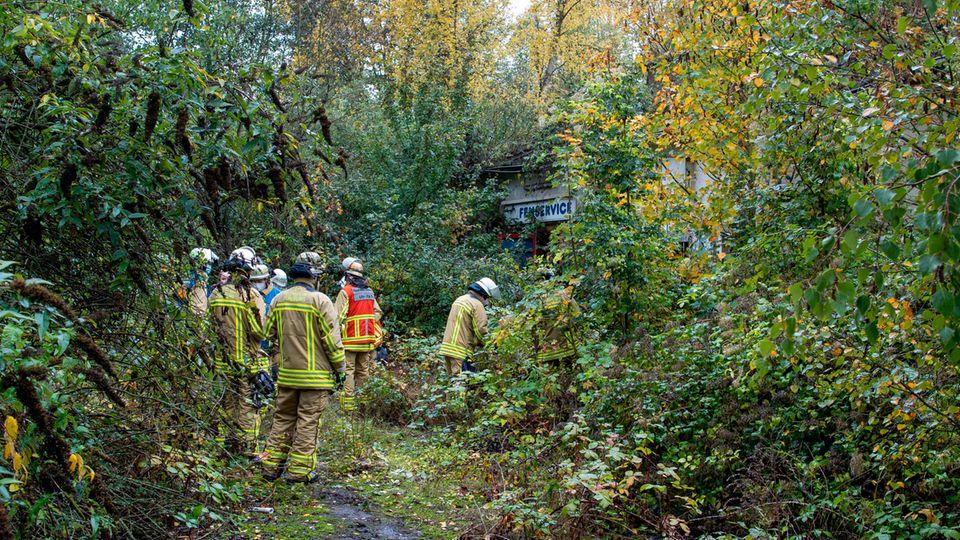 Feuerwehrleute stehen in der Nähe des Fundorts der Leiche eines 14 Jahre alten Mädchens.