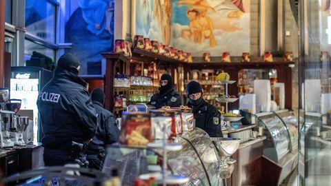 Polizisten stehen in einem Eiscafé im Citypalais in der Duisburger Innenstadt
