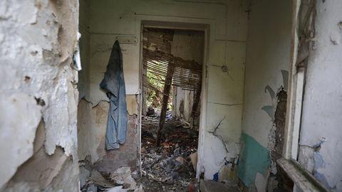 Der Blick durch ein Fenster zeigt den Innenbereich eines Gebäudes, in dem die Leiche eines Mädchens gefunden wurde.