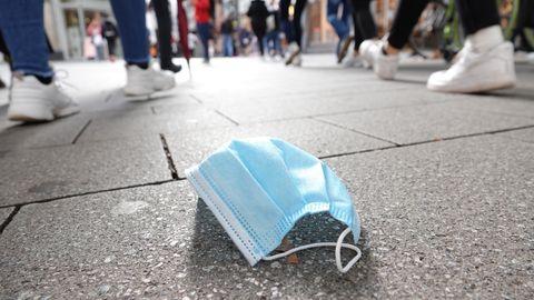 In der Fußgängerzone der Kölner Innenstadt gehen viele Menschen an einer auf dem Boden liegenden Mund-Nasen-Bedeckung vorbei