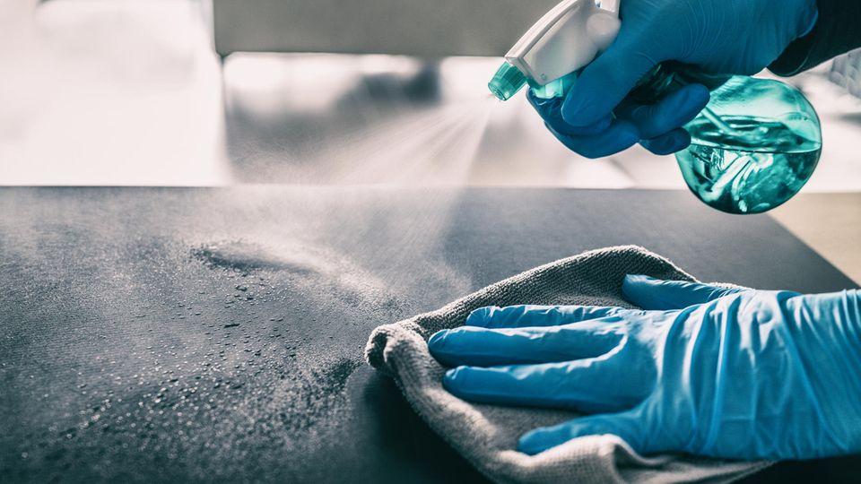 Coronavirus auf Oberflächen: Ein Tisch wird gereinigt