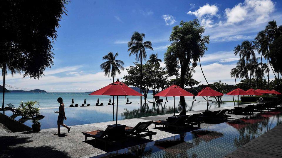 An einem Infinity-Pool stehen liegen unter roten Sonnenschirmen. Doch keine Touristen liegen in der Sonne. Im Hintergrund Palmen