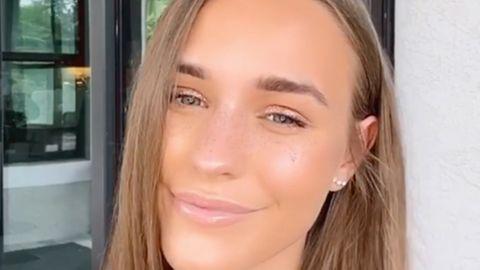 Laura Müller, eine junge Frau mit langen, dunkelblonden Haaren, lächelt mit schräg gelegtem Kopf in die Kamera
